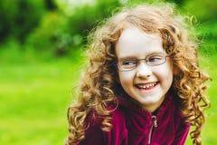 Το γελώντας μικρό κορίτσι eyeglasses σταθμεύει την άνοιξη Στοκ Εικόνα