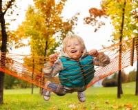 Το γελώντας ξανθό αγόρι βάζει σε καθαρό της αιώρας στο πάρκο Στοκ φωτογραφίες με δικαίωμα ελεύθερης χρήσης