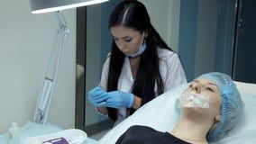 Το γιατρός-cosmetologist θα τυπώσει μια σύριγγα με το hyaluronic οξύ πρίν αρχίζει τη διαδικασία για να αυξάνονται τα χείλια φιλμ μικρού μήκους
