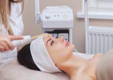 Το γιατρός-cosmetologist κάνει τη διαδικασία θεραπείας Microcurrent μιας όμορφης, νέας γυναίκας σε ένα σαλόνι ομορφιάς στοκ εικόνες