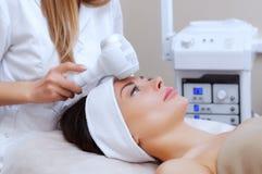 Το γιατρός-cosmetologist κάνει τη διαδικασία Cryotherapy του του προσώπου δέρματος μιας όμορφης, νέας γυναίκας σε ένα σαλόνι ομορ στοκ φωτογραφία