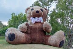 Το γιγαντιαίο βελούδο teddy αφορά ένα πράσινο λιβάδι στοκ εικόνα