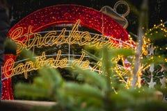 Το γιγαντιαίο κόκκινο σφαιρών Χριστουγέννων οδήγησε όπου γράφεται σε γαλλικό Stras στοκ φωτογραφίες