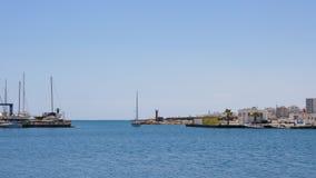 Το γιοτ έρχεται στο θαλάσσιο λιμένα με το μπλε νερό και τον ασυννέφιαστο ουρανό φιλμ μικρού μήκους