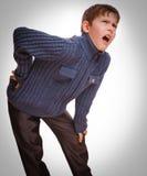 Το γκρίζο εφηβικό αγόρι osteochondrosis κρατά τον έφηβο το χέρι του πίσω Στοκ Εικόνα