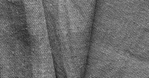Το γκρίζο χονδροειδές ύφασμα βαμβακιού βρίσκεται στις μεγάλες πτυχές στοκ εικόνες