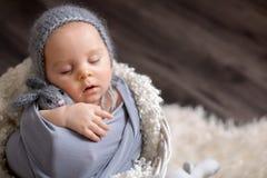 Το γλυκό αγοράκι στο καλάθι, το κράτημα και το αγκάλιασμα teddy αντέχουν, peacef Στοκ Εικόνες