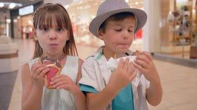 Το γλυκό δόντι, ευτυχείς φίλοι παιδιών τρώει τα μπισκότα και doughnut στο εμπορικό κέντρο απόθεμα βίντεο