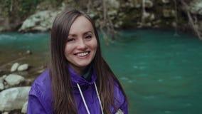 Το γλυκό ευτυχές κορίτσι εξετάζει τη κάμερα και χαμογελά ευρέως στο υπόβαθρο μιας τυρκουάζ λίμνης βουνών απόθεμα βίντεο