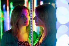 Το γλυκό καυκάσιο κορίτσι περπατά σε έναν λαβύρινθο καθρεφτών με τις ζωηρόχρωμες διόδους και απολαμβάνει ένα ασυνήθιστο δωμάτιο έ στοκ εικόνα
