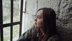 Το γλυκό κορίτσι ανησυχεί λυπημένο και από το παράθυρο με τους φραγμούς απόθεμα βίντεο