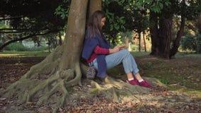 Το γλυκό κορίτσι με ένα smartphone κάθεται κάτω από ένα δέντρο με τις δυνατές άνεμος ρίζες απόθεμα βίντεο
