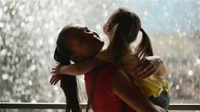 Το γλυκό μικρό κορίτσι αγκαλιάζει και φιλά το όμορφο νέο Mom της Ευτυχής ημέρα μητέρων! Ο καταρράκτης είναι στο υπόβαθρο Οικογένε απόθεμα βίντεο