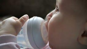 Το γλυκό νερό συνεδρίασης μωρών και από ένα μπουκάλι με εισάγει στο σιφώνιο στην slo-Mo φιλμ μικρού μήκους