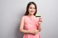 Το γοητευτικό ασιατικό χέρι γυναικών παρουσιάζει πιστωτική κάρτα Παρουσίαση του σπρωξίματός σας στοκ φωτογραφίες