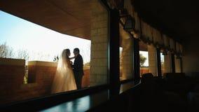 Το γοητευτικό ζεύγος των newlyweds αγκαλιάζει tenderly στο πεζούλι Η νύφη φιλά τον εραστή της στο κεφάλι απόθεμα βίντεο