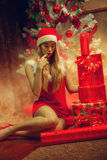 Το γοητευτικό κορίτσι επιλέγει ένα δώρο για τα Χριστούγεννα Στοκ εικόνα με δικαίωμα ελεύθερης χρήσης