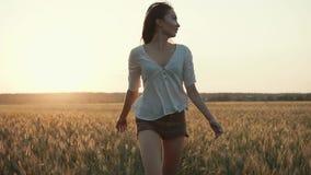 Το γοητευτικό κορίτσι πηδά στον τομέα στην αυγή, κινείται προς τη κάμερα και κοιτάζει γύρω απόθεμα βίντεο