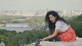 Το γοητευτικό κορίτσι χαλαρώνει στο καρό στο πάρκο και ταΐζει τα περιστέρια απόθεμα βίντεο