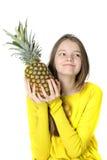 Το γοητευτικό νέο κορίτσι κρατά έναν μεγάλο ώριμο ανανά στα χέρια της στοκ φωτογραφίες