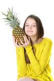 Το γοητευτικό νέο κορίτσι κρατά έναν μεγάλο ώριμο ανανά στα χέρια της στοκ φωτογραφία