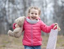 Το γοητευτικό νέο κορίτσι κρατά χαρωπά στα χέρια της ένα συσκευασμένο κιβώτιο με ένα δώρο στοκ εικόνες