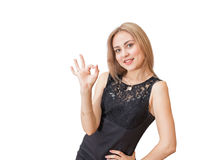 Το γοητευτικό νέο κορίτσι στο κομψό μαύρο φόρεμα παρουσιάζει το σημάδι ΕΝΤΆΞΕΙ Στοκ Εικόνα