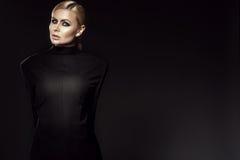Το γοητευτικό ξανθό πρότυπο φορώντας αρσενικό σακάκι πίσω στο μέτωπο με τα όπλα της έδεσε πίσω από την πίσω Στοκ Φωτογραφίες