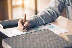 Το γράψιμο επιχειρηματιών κάνει τη σημείωση για τη συνοπτική έκθεση διαγραμμάτων γραφικής εργασίας Στοκ Εικόνες