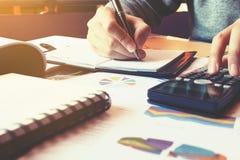 Το γράψιμο επιχειρηματιών κάνει τη σημείωση και υπολογίζει για το κόστος στο σπίτι Στοκ φωτογραφίες με δικαίωμα ελεύθερης χρήσης
