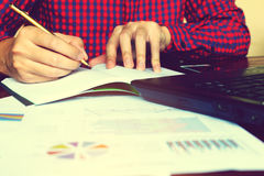 Το γράψιμο επιχειρηματιών κάνει τη σημείωση και υπολογίζει τη χρηματοδότηση στο offi γραφείων Στοκ Εικόνες