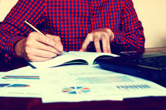 Το γράψιμο επιχειρηματιών κάνει τις σημειώσεις με να υπολογίσουν για το κόστος στο σπίτι Στοκ φωτογραφία με δικαίωμα ελεύθερης χρήσης