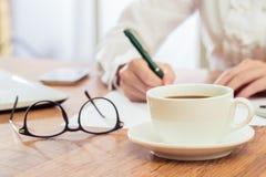 Το γράψιμο επιχειρηματιών και πίνει τον καφέ στο γραφείο Στοκ Εικόνες
