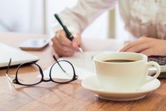Το γράψιμο επιχειρηματιών και πίνει τον καφέ στο γραφείο Στοκ φωτογραφία με δικαίωμα ελεύθερης χρήσης