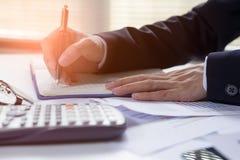 Το γράψιμο επιχειρηματιών στο σημειωματάριο στον ξύλινο πίνακα, άνθρωποι καταγράφει τα λογιστικά στοιχεία που υπολογίζονται από έ Στοκ Εικόνες