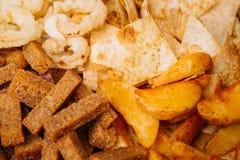 Το γρήγορο φαγητό τσιμπά τη σύνθεση με τα δαχτυλίδια κρεμμυδιών, κροτίδες, που ψήνονται Στοκ Φωτογραφίες