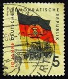 Το γραμματόσημο της ΟΔΓ Γερμανία παρουσιάζει Fritz Heckert αναρρωτικό σπίτι και γερμανική σημαία, circ Στοκ εικόνα με δικαίωμα ελεύθερης χρήσης
