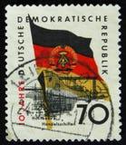 Το γραμματόσημο της ΟΔΓ Γερμανία postape παρουσιάζει Fritz Heckert αναρρωτικό σπίτι και γερμανική σημαία, circa το 1959 Στοκ Φωτογραφία