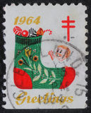 Το γραμματόσημο Χριστουγέννων που τυπώνεται στις ΗΠΑ παρουσιάζει μια γυναικεία κάλτσα με τα δώρα Στοκ Εικόνες