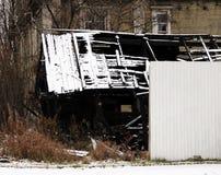 Το γραπτό χιονώδες εγκαταλειμμένο έγκαυμα φωτογραφιών βάζει φωτιά έξω στο ξύλινο σπίτι Στοκ Φωτογραφία