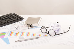Το γραφείο με τις γραφικές παραστάσεις, πληκτρολόγιο, γυαλιά, μάνδρα, τεμάχισε τα έγγραφα και το μπουκάλι του οινοπνεύματος Στοκ φωτογραφία με δικαίωμα ελεύθερης χρήσης