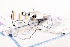 Το γραφείο με τις γραφικές παραστάσεις, πληκτρολόγιο, γυαλιά, μάνδρα, τεμάχισε τα έγγραφα και το μπουκάλι του οινοπνεύματος Στοκ φωτογραφίες με δικαίωμα ελεύθερης χρήσης