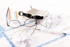 Το γραφείο με τις γραφικές παραστάσεις, πληκτρολόγιο, γυαλιά, μάνδρα, τεμάχισε τα έγγραφα και το μπουκάλι του οινοπνεύματος Στοκ Φωτογραφία