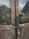 Το γυαλί στην παλαιά ξύλινη πόρτα, στην επιφάνεια της αντανάκλασης του βουνού και του κτηρίου Στοκ Εικόνα