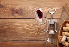 Το γυαλί, το ανοιχτήρι και το κύπελλο κόκκινου κρασιού με βουλώνουν Στοκ Εικόνες