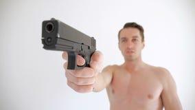 Το γυμνό άτομο στοχεύει το πυροβόλο όπλο του στο άσπρο υπόβαθρο φιλμ μικρού μήκους