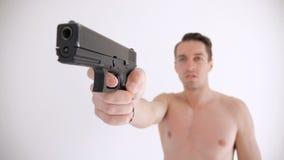 Το γυμνό άτομο στοχεύει το πυροβόλο όπλο του στο άσπρο υπόβαθρο απόθεμα βίντεο