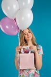 Το γλυκό κορίτσι με τα baloons και τα μικρά prersents τοποθετούν σε σάκκο στα χέρια στο μπλε υπόβαθρο Στοκ εικόνα με δικαίωμα ελεύθερης χρήσης