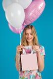 Το γλυκό κορίτσι με τα baloons και τα μικρά prersents τοποθετούν σε σάκκο στα χέρια στο μπλε υπόβαθρο Στοκ Φωτογραφίες