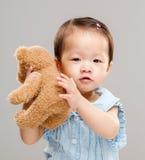 Το γλυκό κοριτσάκι αγκαλιάζει την κούκλα παιχνιδιών της στοκ εικόνες